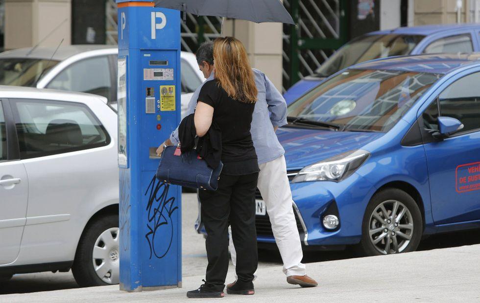¿Quién debería gestionar la ORA?.Una pareja pagando la ORA en uno de los parquímetros instalados en San Agustín.