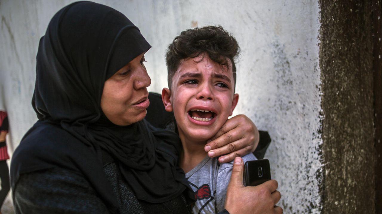 El hermano de uno de los menores palestinos muertos, que tenía 15 años, llora desconsolado durante su funeral, en Gaza