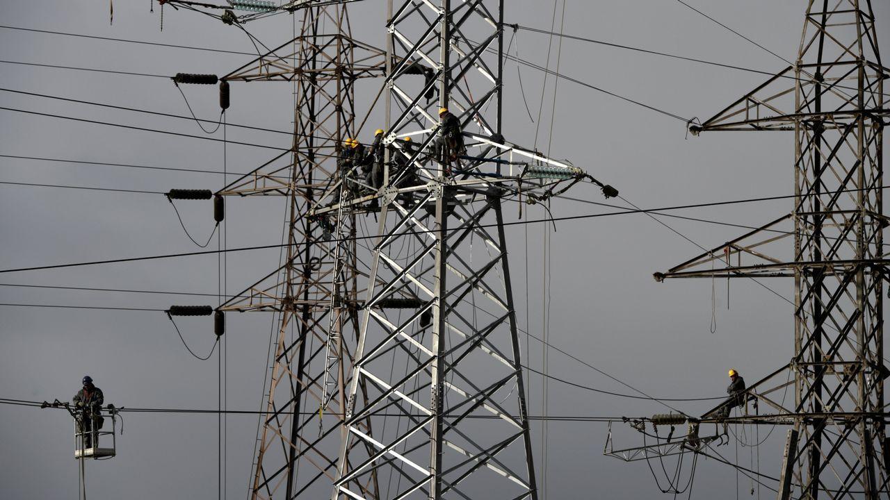 Varios trabajadores intentan arreglar los desperfectos de una red de electricidad en Gijón.