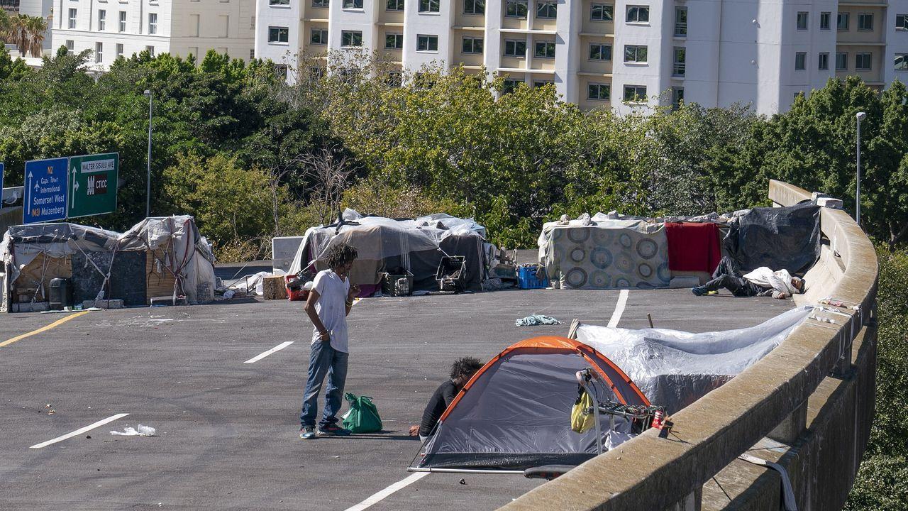 Dos personas sin hogar preparan su tienda de campaña en la ciudad de Cape Town, durante el tercer día de confinamiento en Sudáfrica