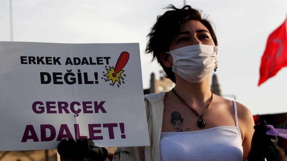 Una mujer con mascarilla muestra un letrero que dice  ¡No justicia masculina! ¡Justicia verdadera!  Mientras los manifestantes mantienen la distancia social agarrándose a cintas moradas, en Estambul, Turquía