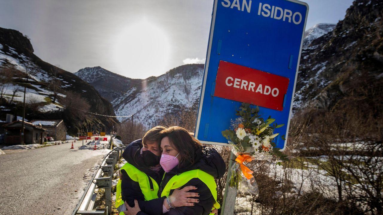 Dos mujeres rinden homenaje a los trabajadores sepultados en San Isidro colocando un ramo de flores