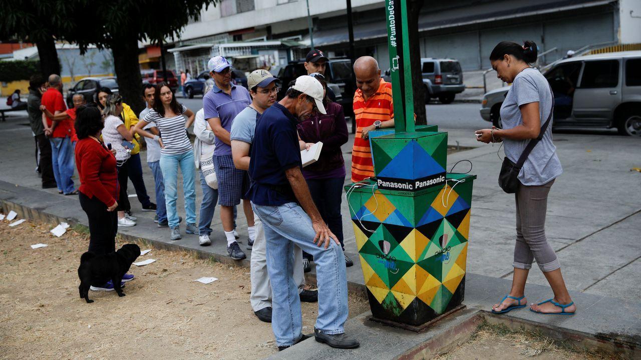 Recarga de móviles en un puesto de energía solar en Caracas