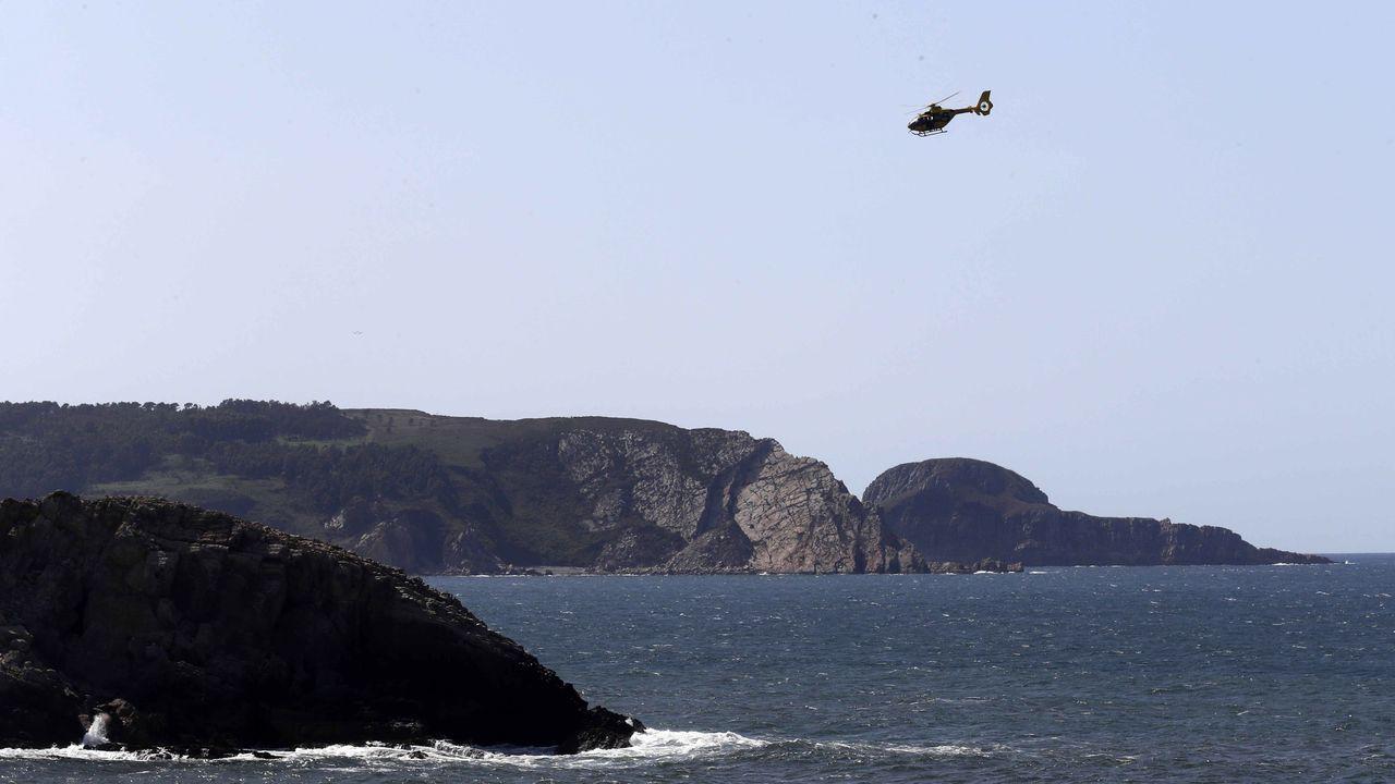 Uno de los helicópteros de Bomberos de Asturias rastrea hoy la zona en la que una mujer de 35 años desapareció la pasada noche tras caer al mar cuando pescaba en la localidad de Arnao, en el municipio asturiano de Castrillón