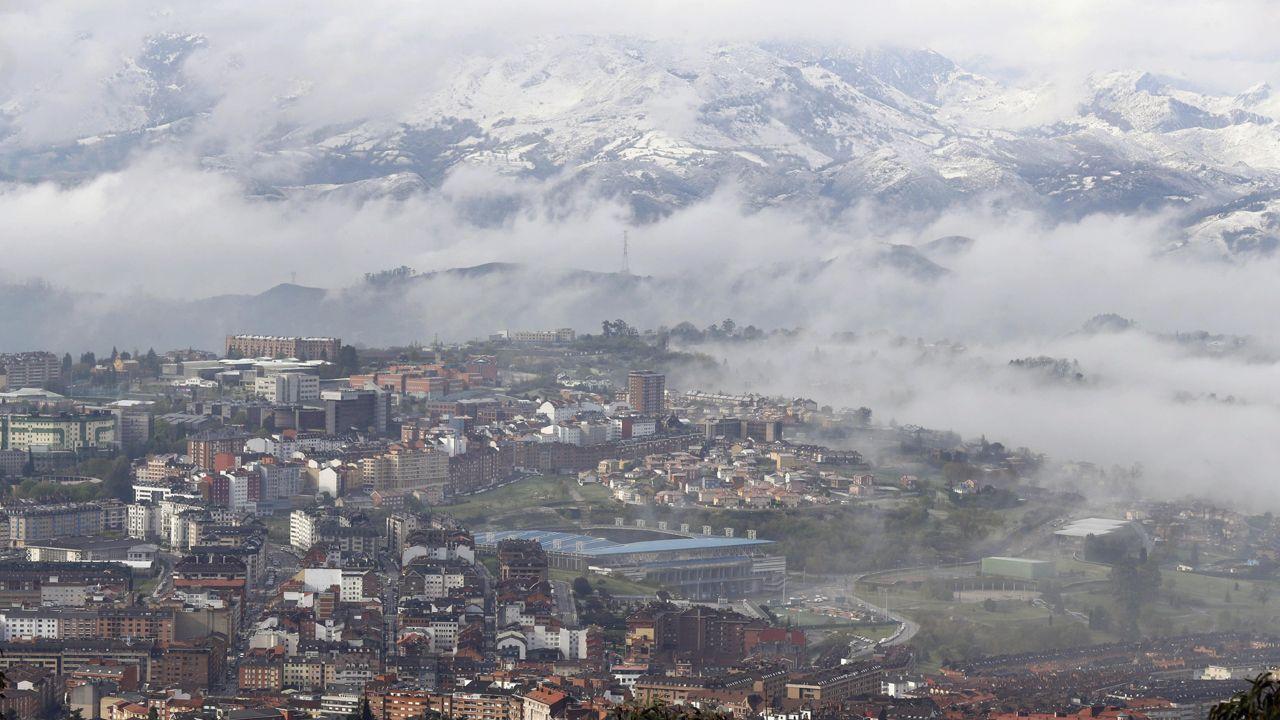 contaminación, polución .Vista general de Oviedo, cubierto de nubes y con las montañas nevadas al fondo