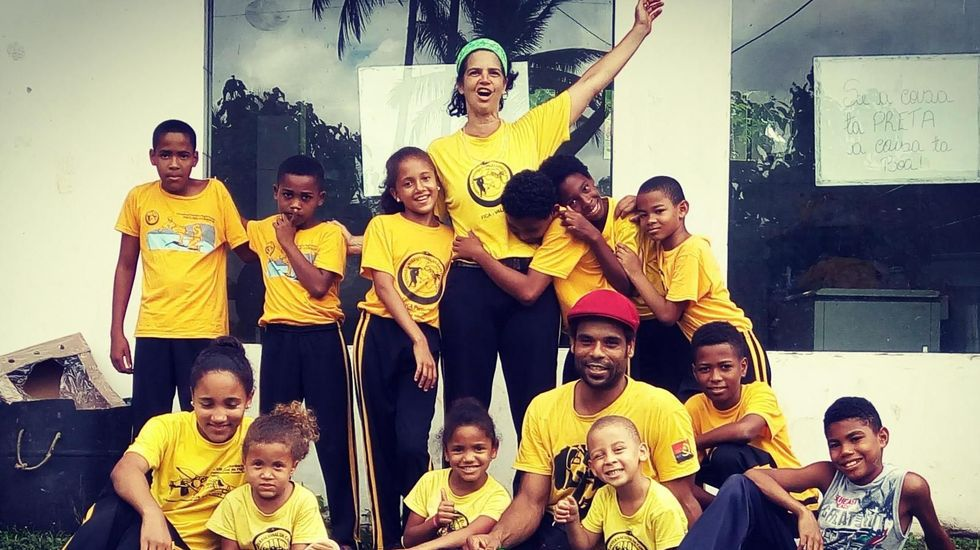 Maria Eugenia Poggi (Mestra Gege) junto algunos de los niños de Graciosa a los que van dirigidos los juguetes y el material escolar recaudado por el grupo Capoeira Angola FICA Compostela