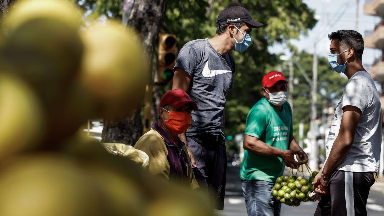 Vendedores ambulantes de fruta llevan mascarillas mientras trabajan en la capital de Paraguay, Asunción