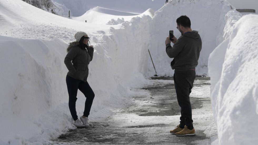 Carretera abierta alrededor de la nieve en Somiedo.Una pareja se saca fotos en un pasillo de nieve en Pajares