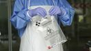 Un sanitario sostiene una bolsa con una muestra para realizar un análisis PCR