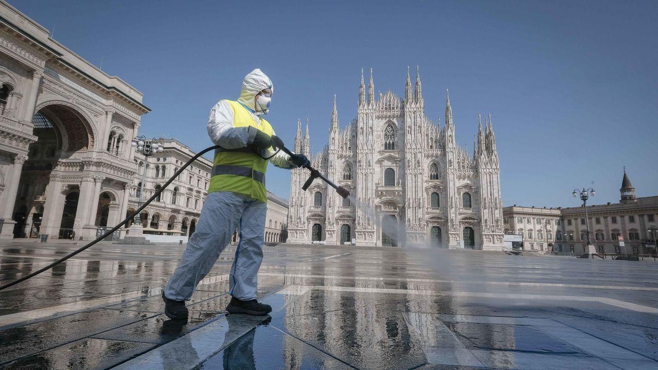 Un trabajador limpia la plaza del Duomo de Milán