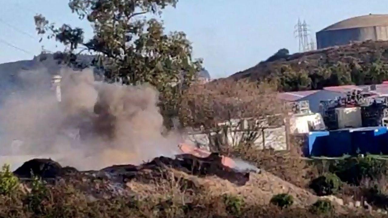 Operarios remueven los restos en la zona del incendio de la planta de compostaje.Baldomero Vázquez, concejal de Hacienda de Arteixo