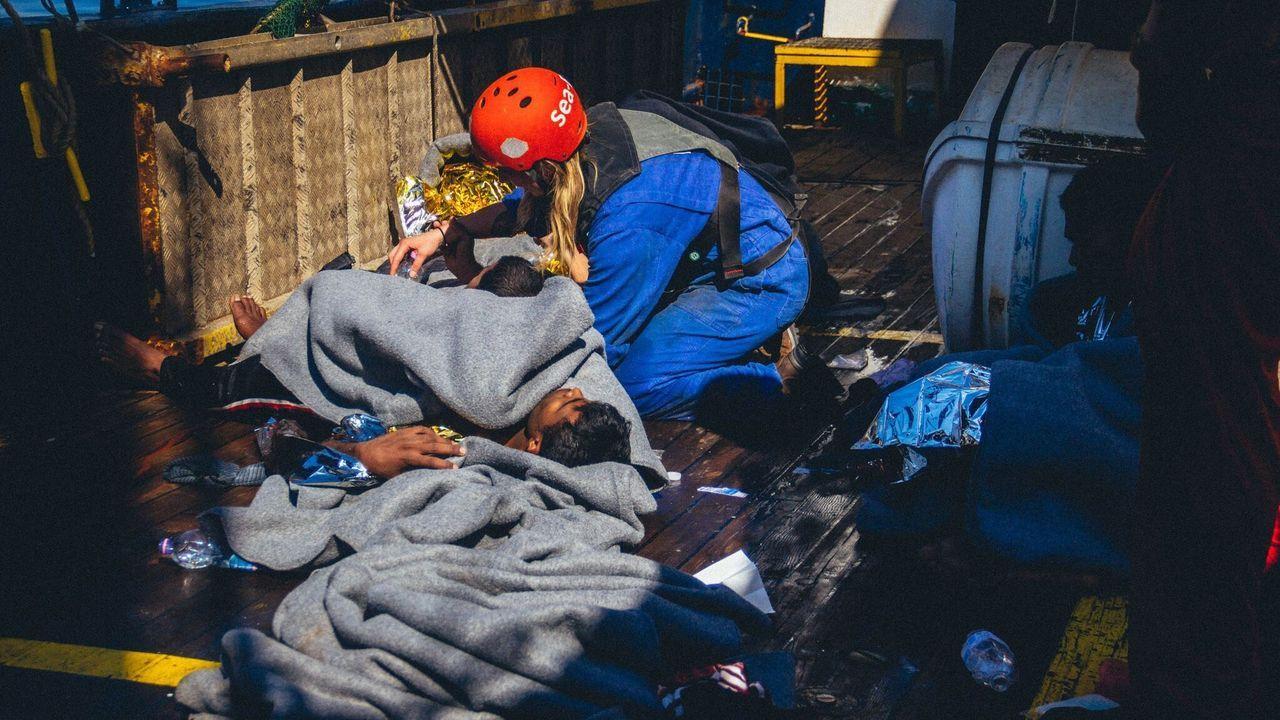 Un miembro de Sea Eye atiende a uno de los 150 migrantes rescatados por el Alan Kurdi
