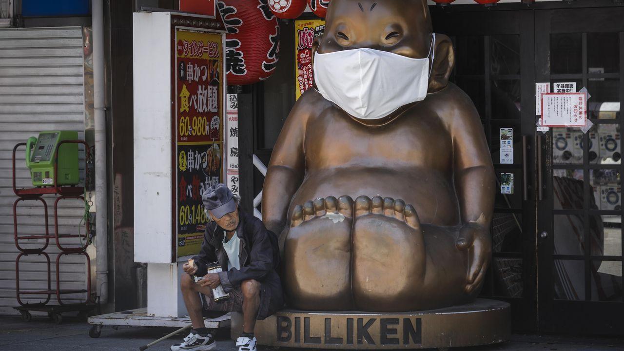 Un hombre, ayer, sentado junto a la deidad local Billiken, de Osaka