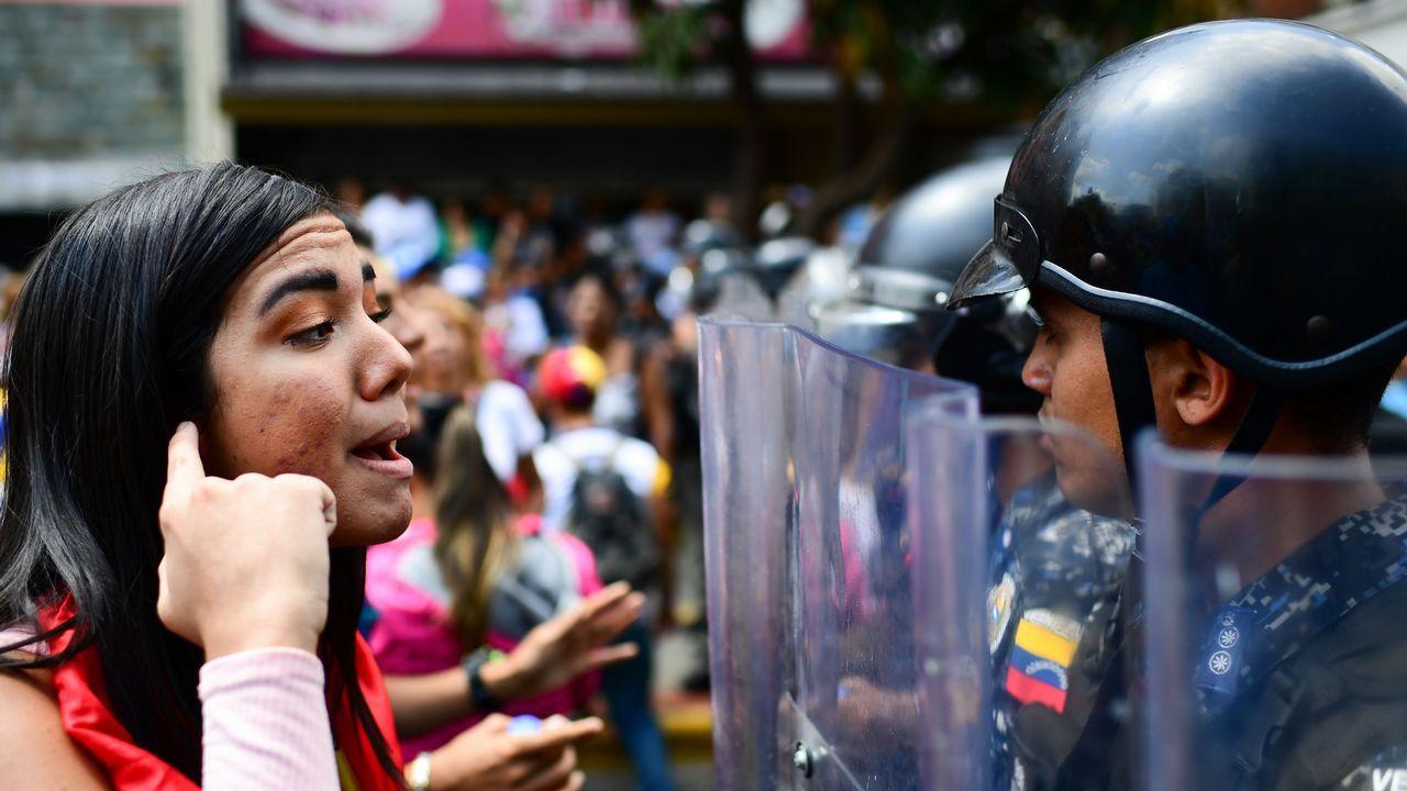 Una partidaria de Guaidó se enfrenta a un miembro de la Policía Bolivariana durante la manifestación de ayer en Caracas