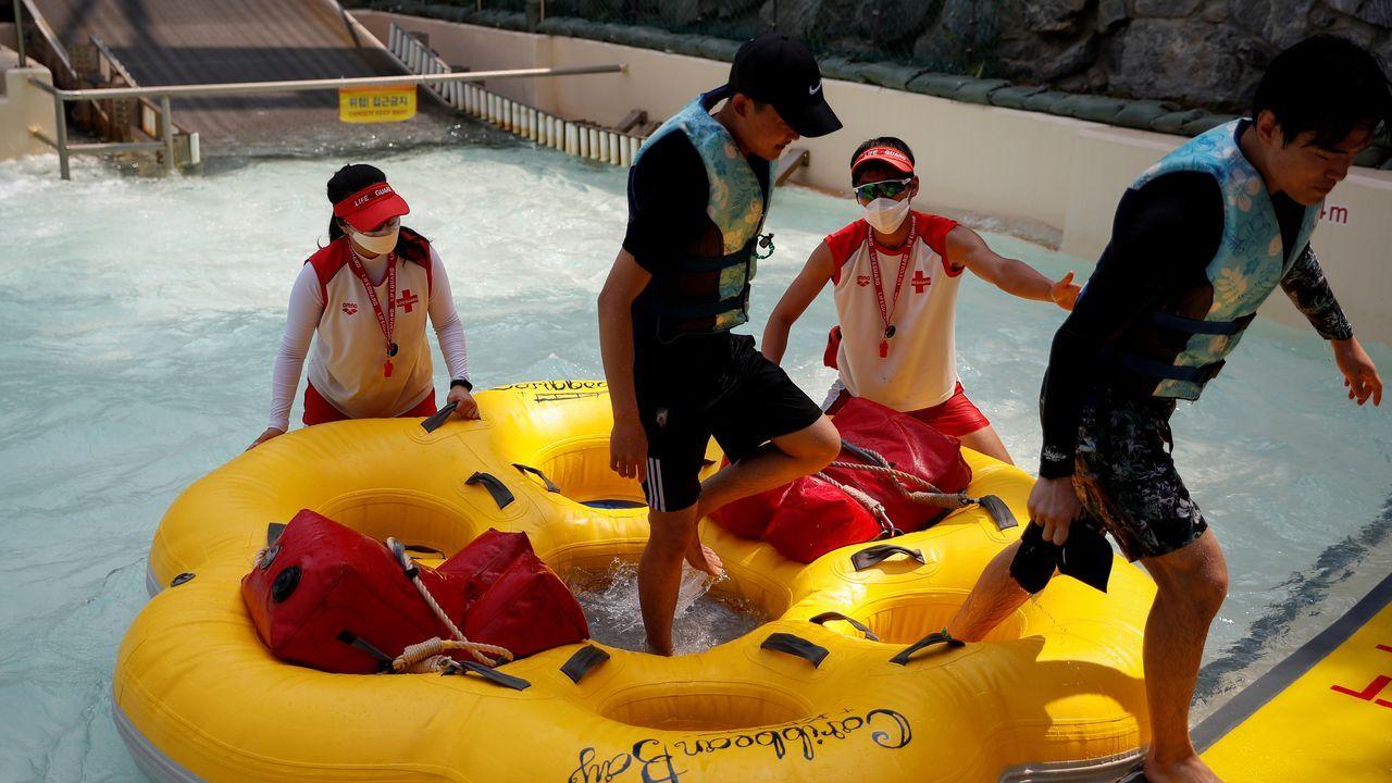Los empleados de un parque acuático de Corea del Sur llevan mascarilla mientras ayudan a los visitantes