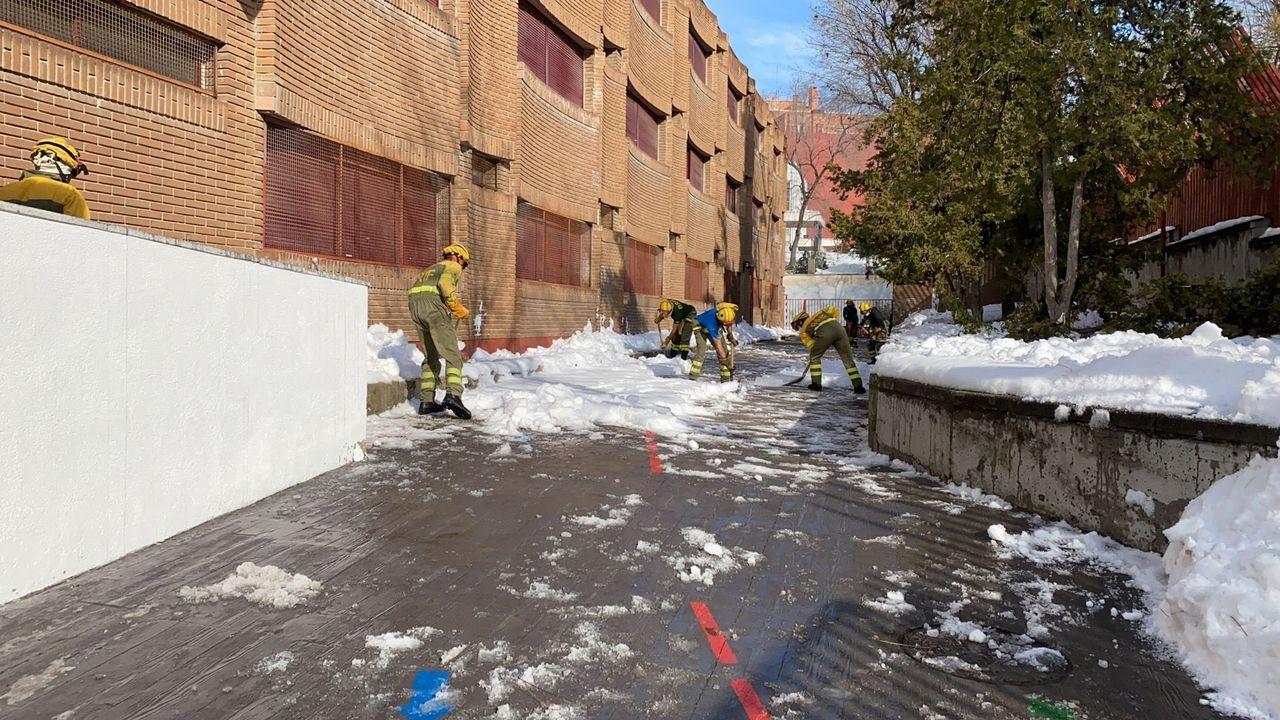 unos vecinos tratan de quitar la nieve de sus vehiculos en el pueblo de Pajares