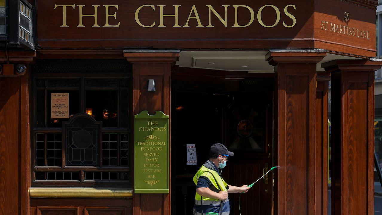 Un hombre desinfectaba hoy por la mañana un pub en Londres, en St Martin's Lane, en el área de Covent Garden y Charing Cross