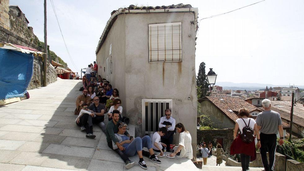 Visitantes de la feria se protegen del sol en la zona de los puestos de comida de A Régoa
