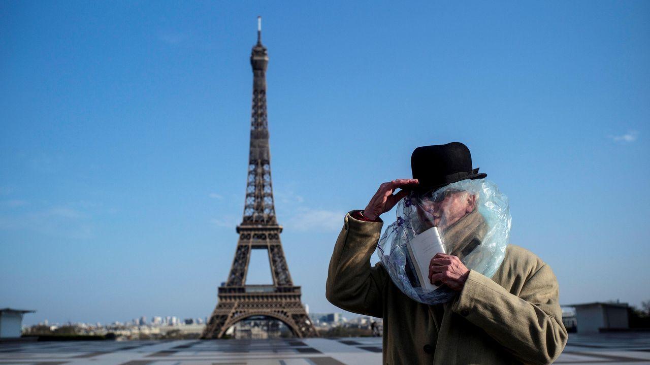 Un hombre cubierto con una bolsa de plástico lee un libro frente a la Torre Eiffel, en París