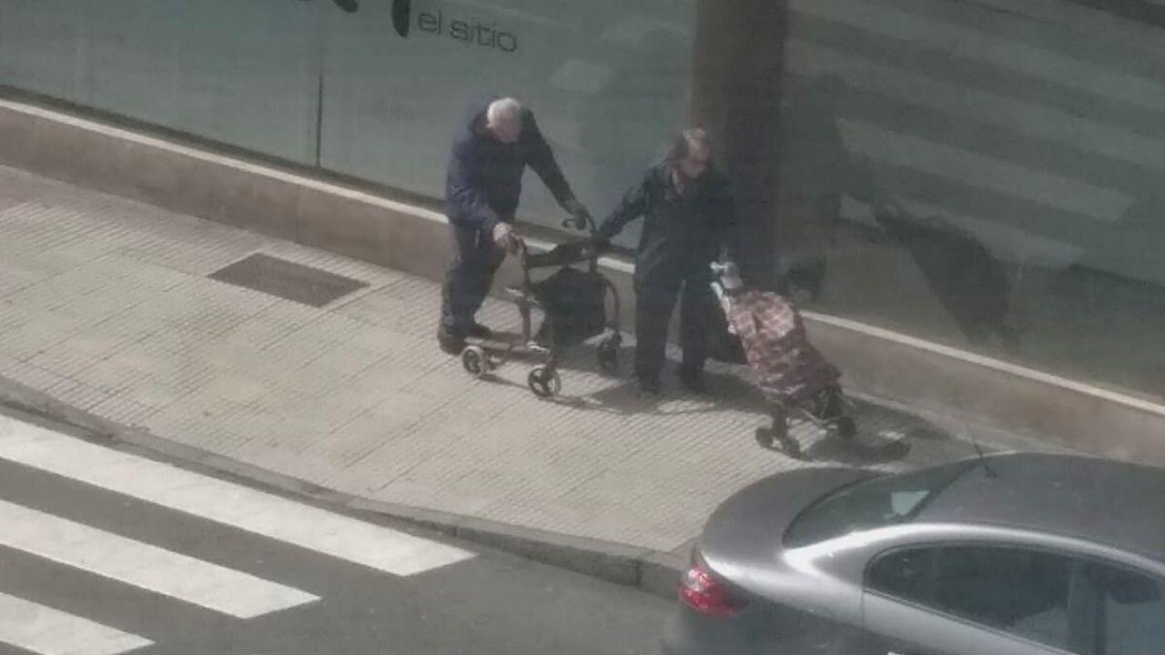 Una pareja de ancianos, con un carrito de la compra y un andador, por una calle de Gijón, durante esta crisis sanitaria