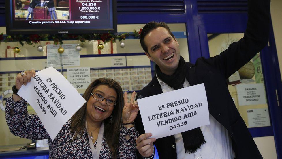 Marcos Delgado, dueño de la administración de lotería ubicada en la calle Condesa de Venadito, en Madrid, acompañado de la vendedora Jenyffer Hoyos celebran el segundo premio, que ha recaído en el 04536, vendido en parte en esta administración