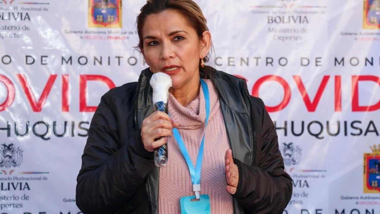 La presidenta de Bolivia con la tarjeta «antivirus» al cuello