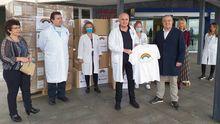 El gerente del área sanitaria IV, Luis Hevia, recibe la camiseta de la campaña solidaria de manos del empresario de 3hmas1, Jesús Fernández.