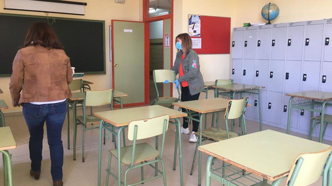 Varias docentes separan y colocan las mesas de un aula del IES Monte Naranco