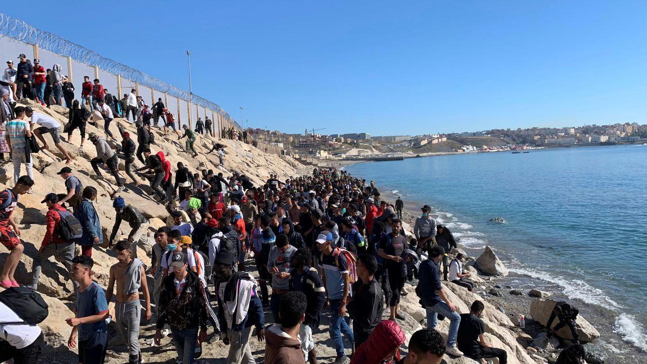Un grupo de personas aguardan junto a la valla fronteriza que separa Fnideq, en Marruecos, y Ceuta