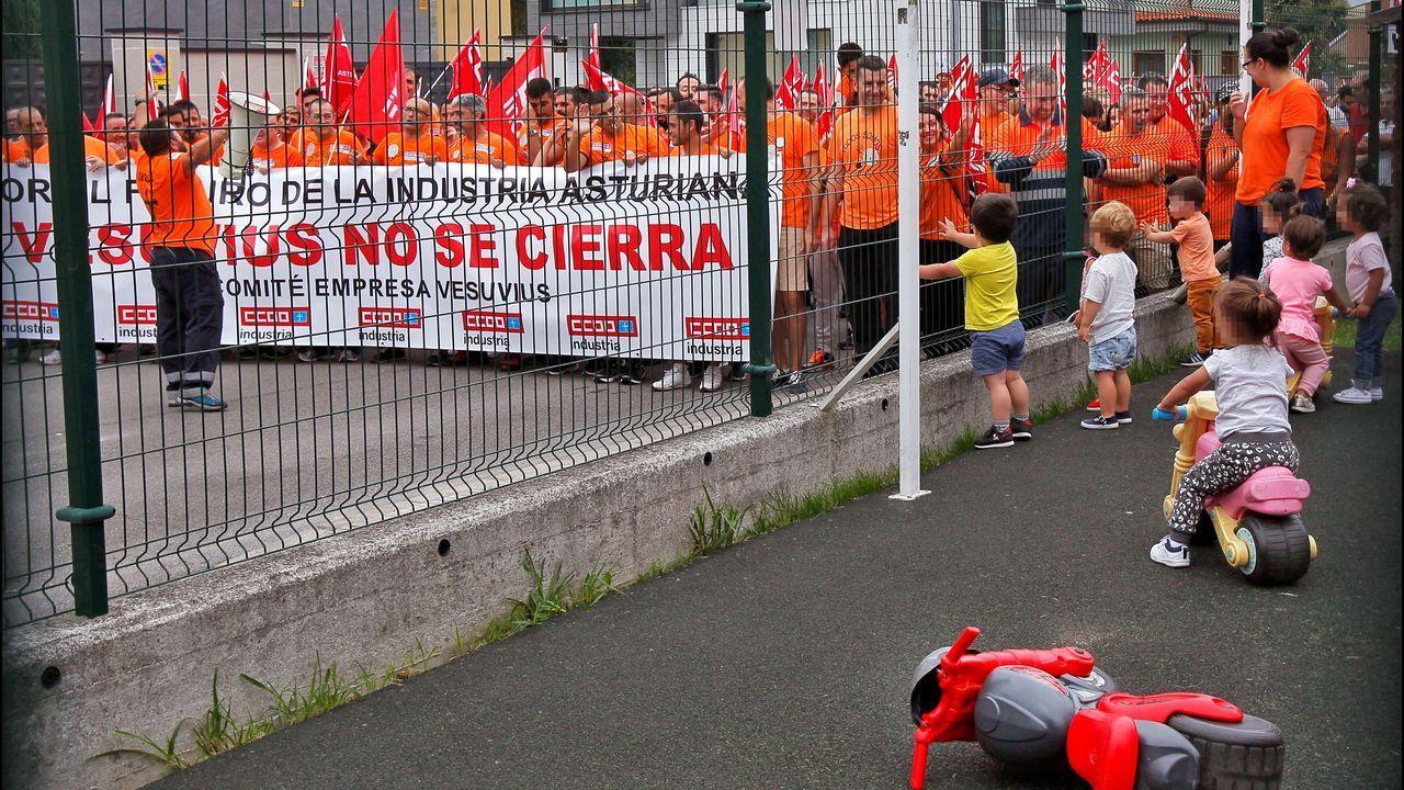 Un grupo de niños observa el paso de los cientos de personas que participan este lunes en la marcha a pie desde la planta de Vesuvius en Riaño hasta el Ayuntamiento de Langreo para protestar contra la desindustrialización de las cuencas mineras