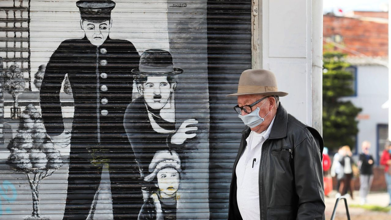 Un hombre, con mascarilla, camina por una calle de Bogotá