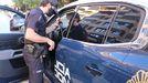 Un agente de la Policía Nacional junto a un coche patrulla
