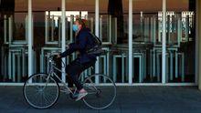 Una mujer pasa en bicicleta ante un bar cerrado por la pandemia en Barcelona
