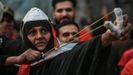 Una  mujer usa un tirachinas contra las fuerzas del orden en la calle Al Rasheed de Bagdad