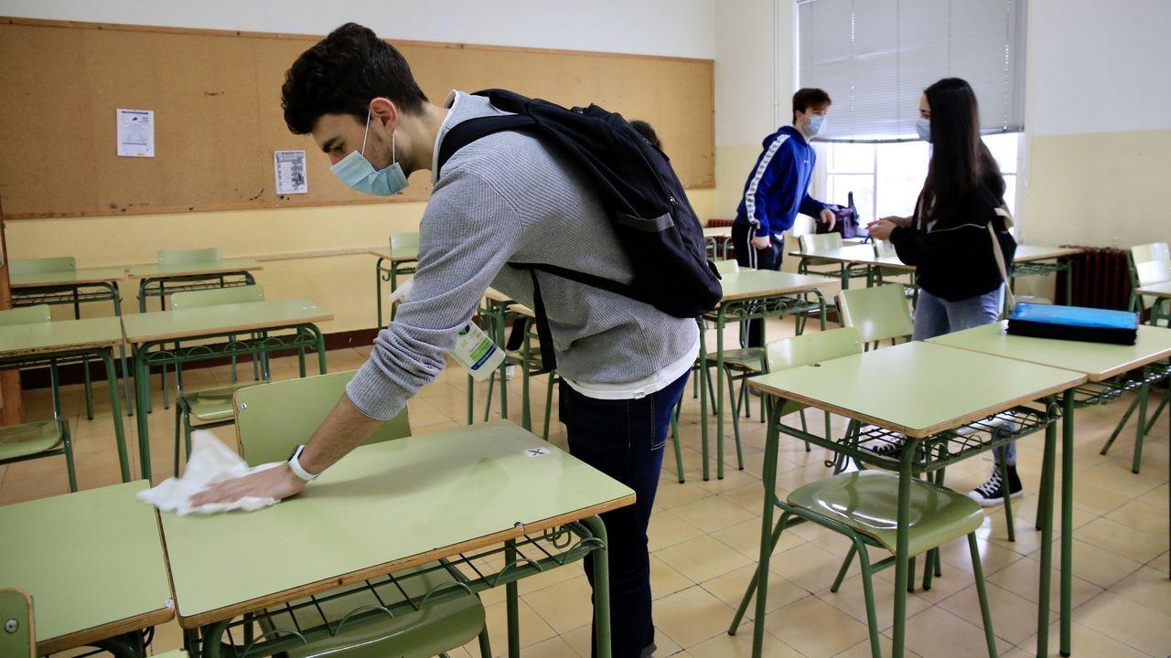 Regreso a las aulas en Ribeira.Alumnos desinfectan las mesas en el IES Ollos Grandes de Lugo