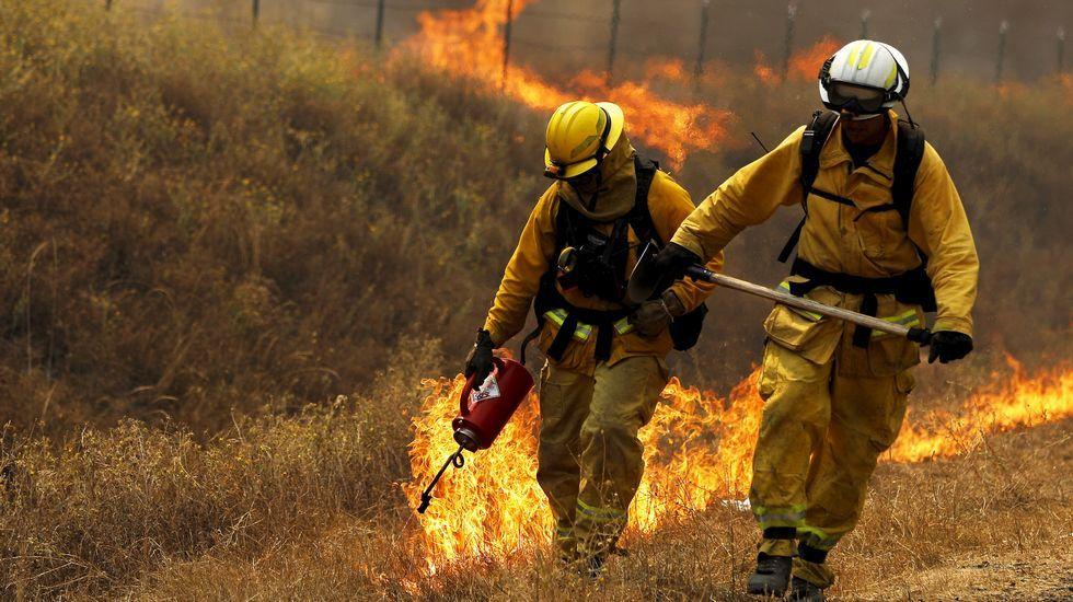 Dos bomberos cargados con sus herramientas durante los incendios de Lower Lake, en California