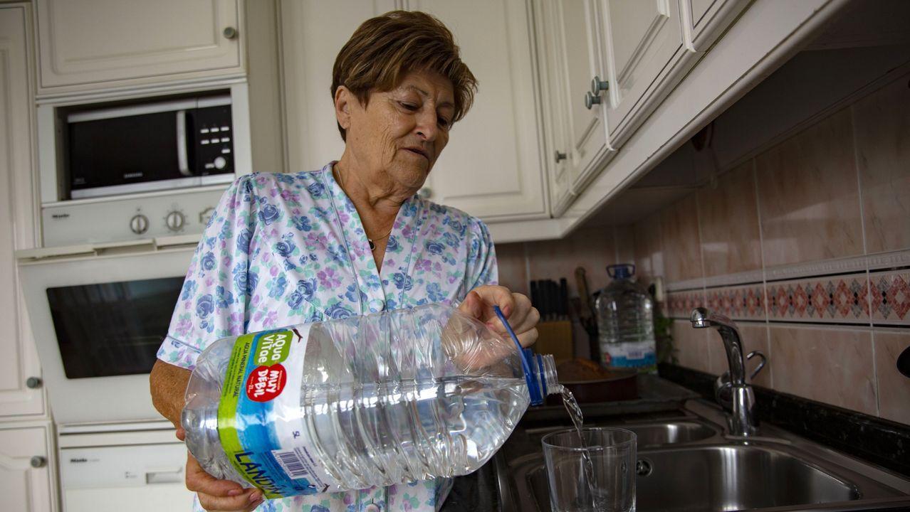 Una vecina usaba agua, ayer martes, de una de las garrafas entregadas gratuitamente por el Concello de Ponteceso