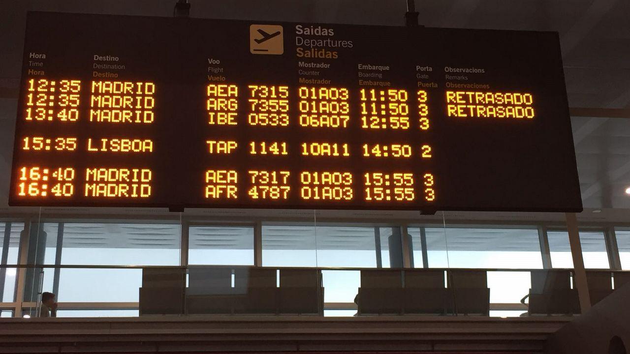 Un grupo de pasajeros consulta los vuelos en el Aeropuerto de Asturias.Pedro Sánchez