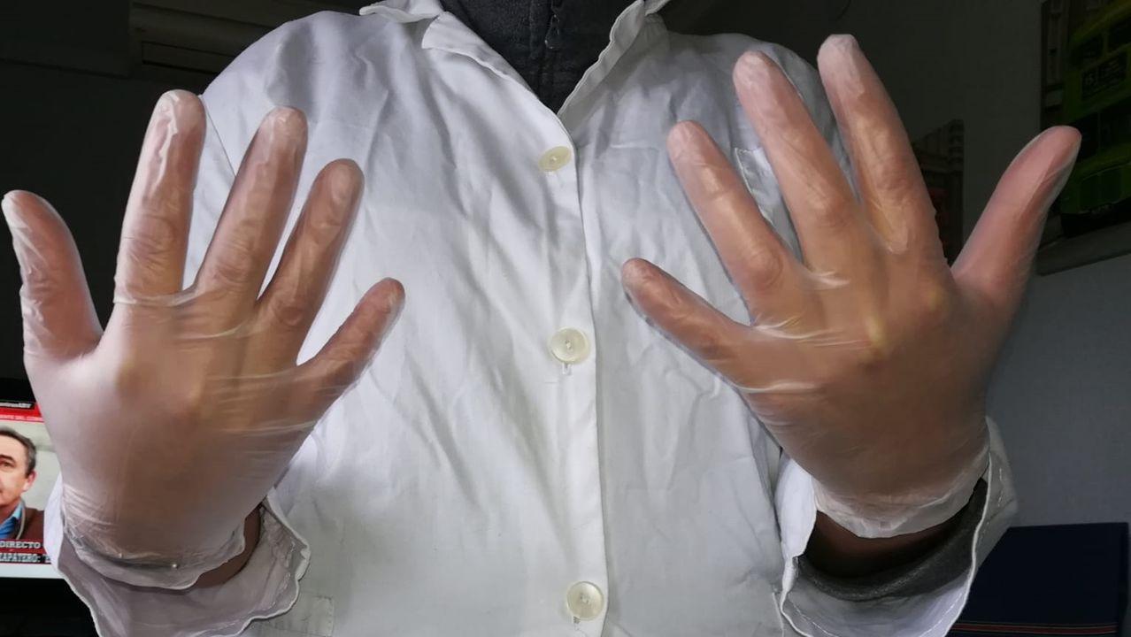 Una trabajadora del servicio de ayuda a domicilio muestra su equipo de protección, unos guantes y una bata de tela