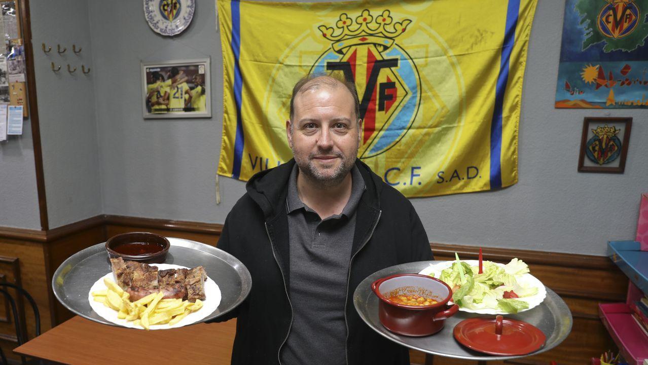 El gerente del bar Abrente muestra en el local uno de sus emblemas, la tapa de churrasco.  Detrás, conserva con orgullo, y entre muchos recuerdos del Compos, la bandera del Villarreal, el equipo de su provincia natal