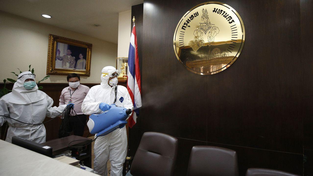 Varios trabajadores desinfectan las instalaciones del Gobierno de Bangkok
