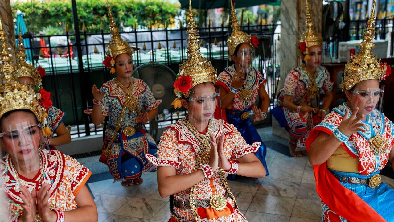 Artistas del Santuario de Erawan, en Tailandia, lucen máscaras protectoras durante su actuación