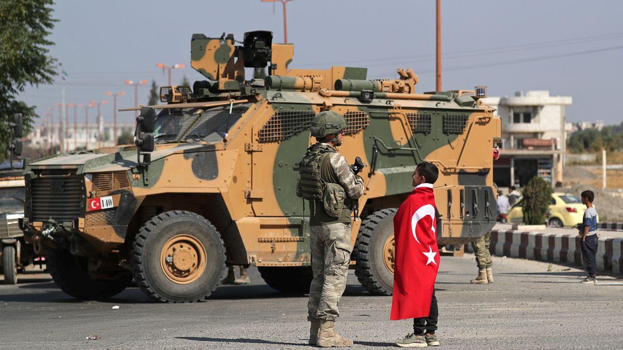 Un niños vestido con la bandera turca saluda a uno de los soldados despelgados en Tal Abiad