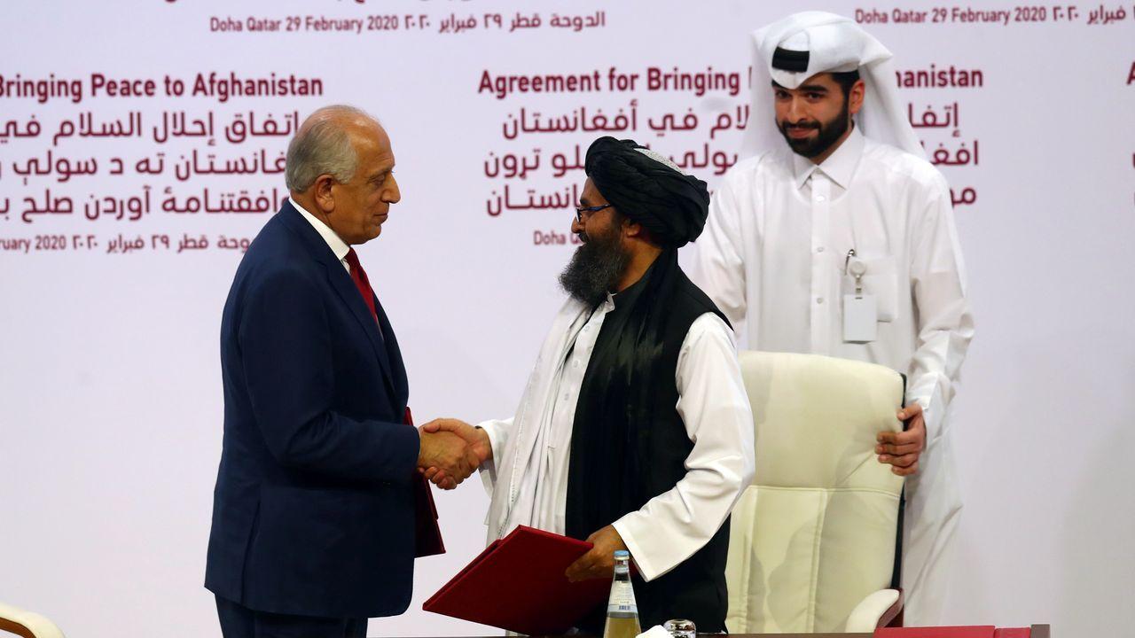 Los representantes de Estados Unidos (izquierda) y de los talibanes tras suscribir el histórico acuerdo de paz en Doha
