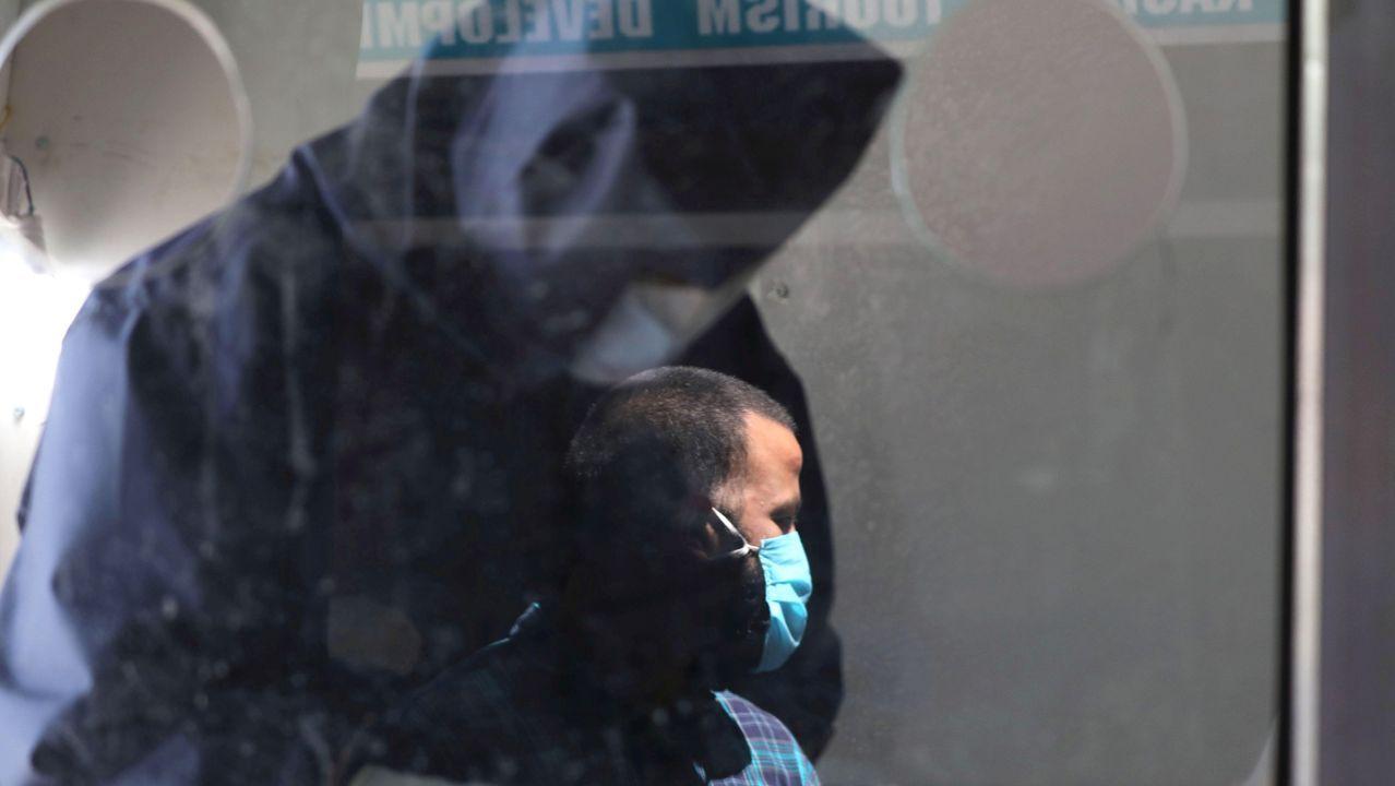 En Cachemira, un hombre se ve reflejado en el cristal de una unidad móvil en la que están realizando pruebas de covid-19