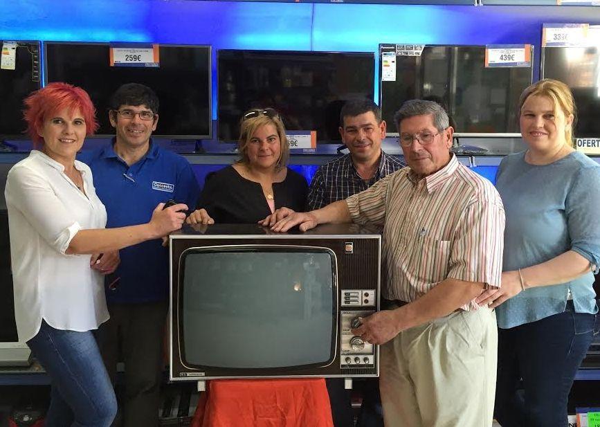 La nueva generación Rey posa con su padre, Manuel Rey, y con uno de los televisores que él fabricó.