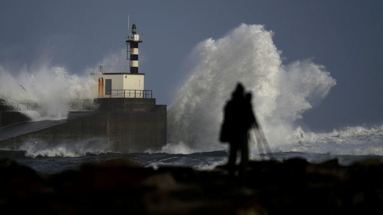 Un hombre intenta sacar fotos del temporal en San Esteban de Pravia, Asturias.