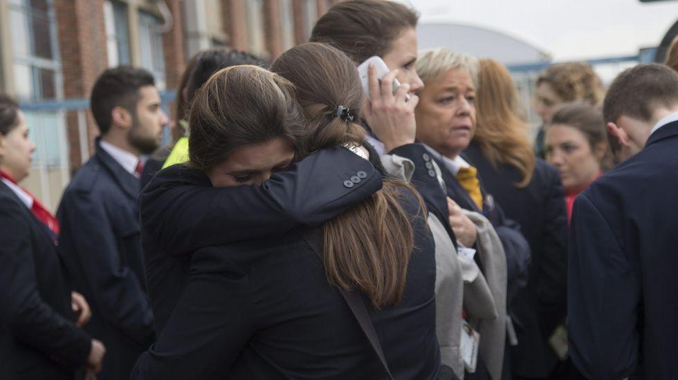 Unas trabajadoras del aeropuerto se abrazan tras ser evacuadas junto a los pasajeros del aeropuerto después de que se registraran las explosiones