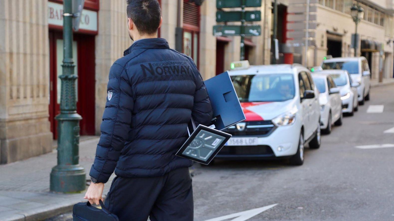 Un trabajador portando su ordenador para teletrabajar, en una calle de Vigo