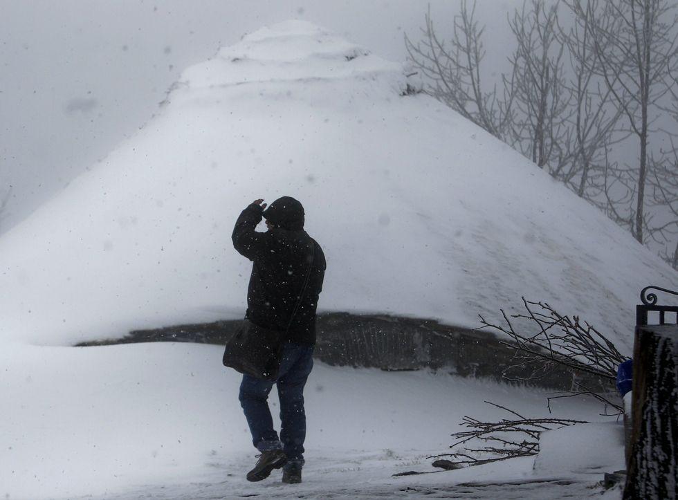 Un visitante retratando ayer la palloza de Galán, en Pedrafita, sepultada por la nieve.